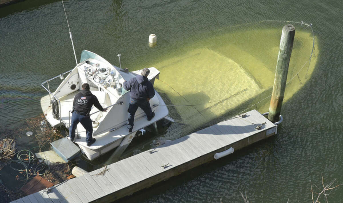 Hour Photo/Alex von Kleydorff Norwalk Marine Police and property managers investigate a boat that sunk at the dock at Shore Point Marina on the Norwalk River on Wednesday