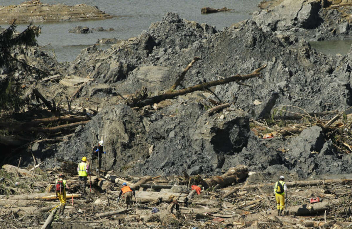 Workers search an area next to large mounds of dirt Tuesday, April 1, 2014, near Darrington, Wash., in the debris field of the deadly mudslide that hit the community of Oso,Wash. on March 22, 2014. (AP Photo/Ted S. Warren)