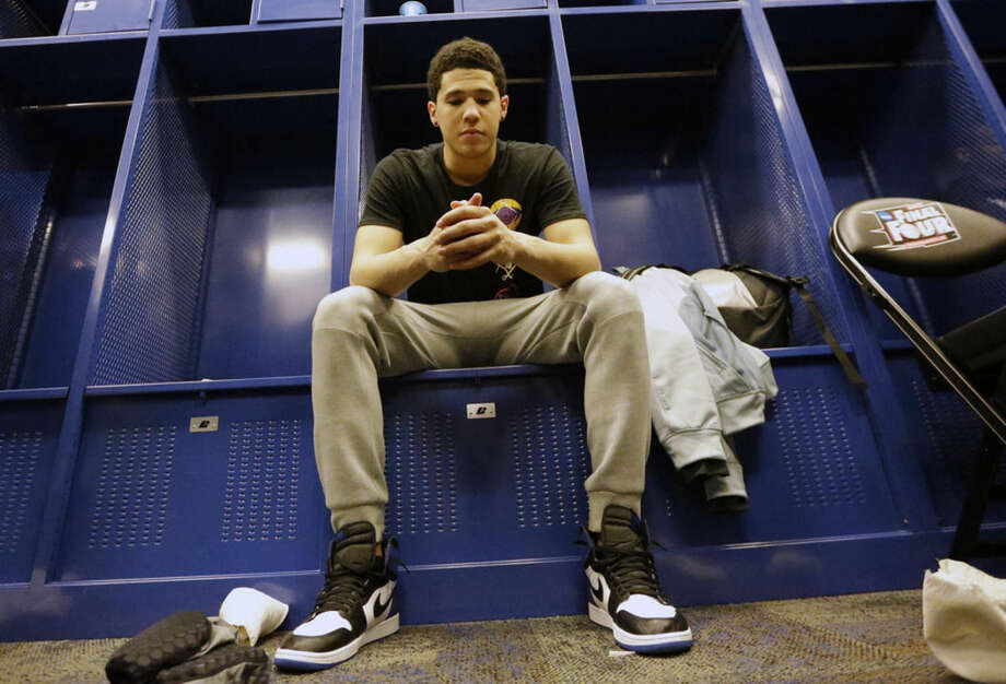 Kentucky's Devin Booker sits in the locker after the NCAA Final Four tournament college basketball semifinal game against Wisconsin Saturday, April 4, 2015, in Indianapolis. Wisconsin won 71-64. (AP Photo/David J. Phillip)