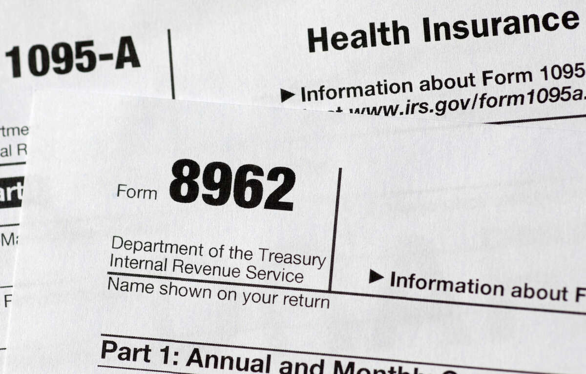 FILE - In this Aug. 21, 2014 file photo shows health care tax forms 8962 and1095-A, in Washington. As the April 15 tax deadline nears, people who got help paying for health insurance under President Barack Obama's law are seeing the direct effect on their refunds _ hundreds of dollars, for better or worse. With subsidies tied to income, consumers must accurately estimate what they will make for the coming year _ and that's been a challenge. Guess on the low side, get more help now with premiums, but owe money later at filing time. Overestimate income, expect bucks back from the taxman. (AP Photo/Carolyn Kaster)