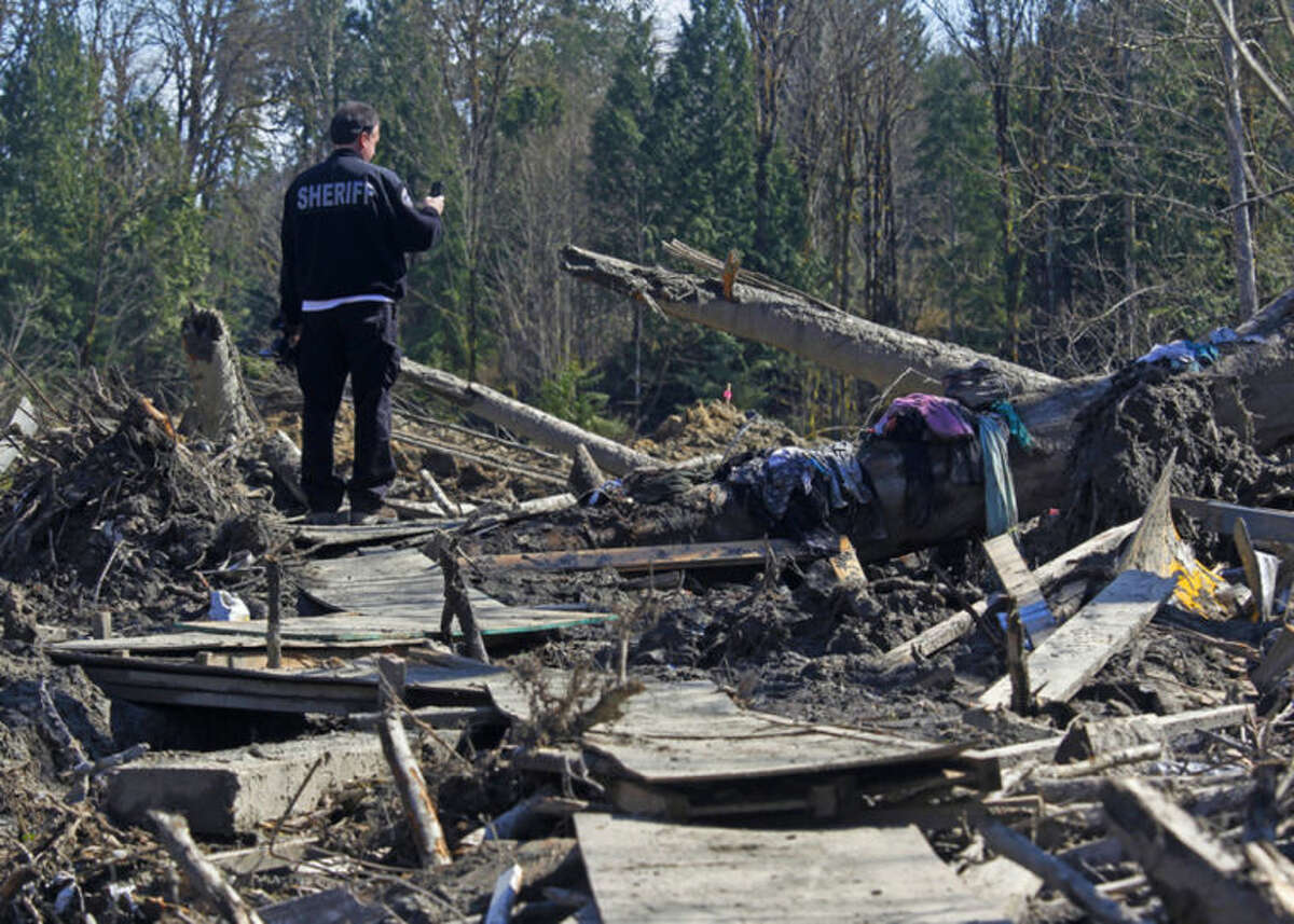 A sheriff official takes photos of debris from a massive fatal mudslide near Oso, Wash., on Tuesday, April 1, 2014. The March 22 mudslide destroyed a rural mountainside community northeast of Seattle. (AP Photo/The Herald, Mark Mulligan) MANDATORY CREDIT.