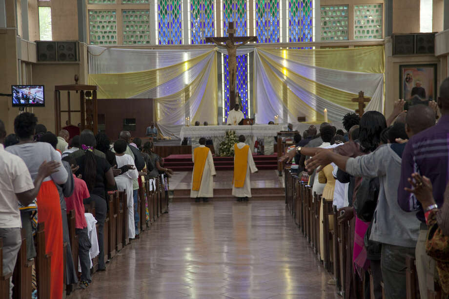 Kenyan Christians pray as they join a morning service at Holy Family Basilica in Nairobi, Kenya, Sunday, April 5, 2015, during Easter Sunday when Christians celebrate the resurrection of their Lord, Jesus Christ, according to Scripture after his crucifixion on the cross. Special prayers were held Sunday for the victims of the recent Garissa University Attack, when Al-Shabab gunmen rampaged through the university in northeastern Kenya on Thursday, killing scores of people. (AP Photo/Sayyid Azim)