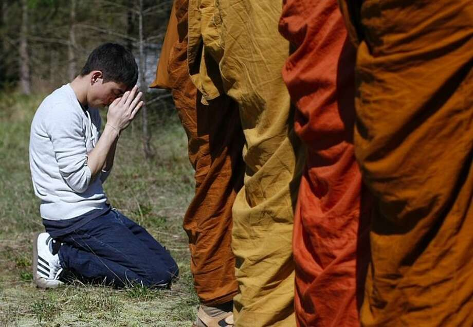 Adisorn Gronski, left, prays while monks from the Atammayatarama Buddhist Monastery in Woodinville chant for victims of a deadly mudslide near a west side road block, Tuesday, April 1, 2014, in Oso, Wash. The March 22 mudslide destroyed a rural mountainside community northeast of Seattle. (AP Photo/The Herald, Sofia Jaramillo) MANDATORY CREDIT.