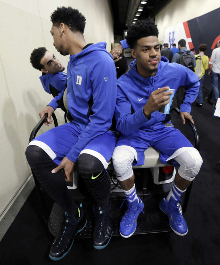Duke's Tyus Jones, from left, Jahlil Okafor and Quinn Cook get a ride after a news conference for the NCAA Final Four college basketball tournament championship game Sunday, April 5, 2015, in Indianapolis. (AP Photo/Charlie Neibergall)