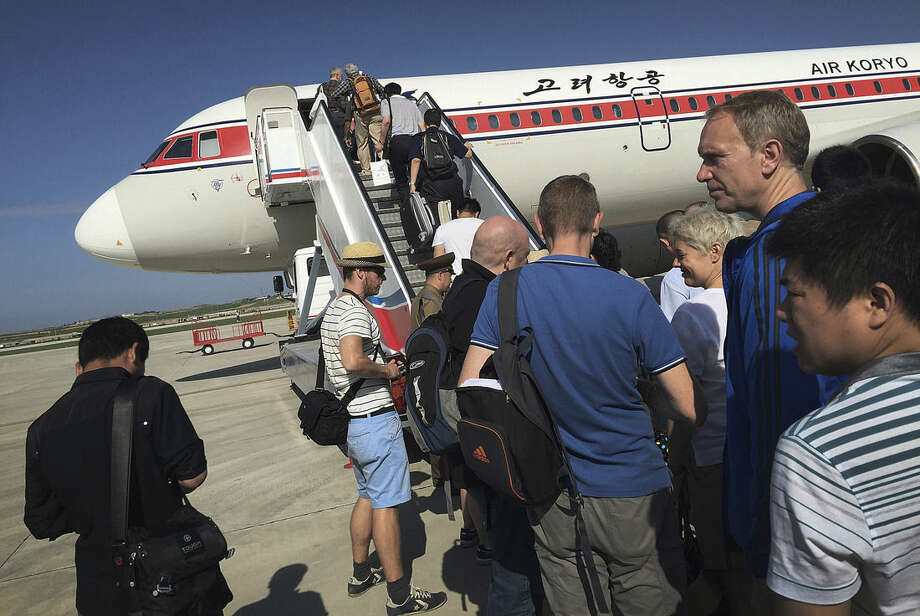 FILE - In this June 27, 2015, file photo, passengers board an Air Koryo plane bound for Beijing, at the Pyongyang International Airport in Pyongyang, North Korea. Without banning it outright, the U.S. State Department has long warned against travel to North Korea. But, post purported H-bomb test, the U.S. is now reportedly seeking a ban on tourism and restrictions to keep the North's flagship airline, Air Koryo, from flying into and out of airports abroad. Most tourists board their flights to Pyongyang from Beijing. (AP Photo/Wong Maye-E, File)