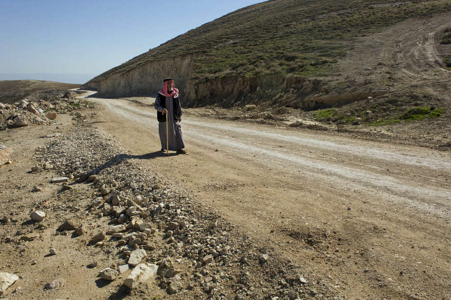 In this Jan. 16, 2016 photo, a Palestinian walks on a newly-made section of a road that was financed by the European Union, on the outskirts of the West Bank village of Taqoa, near Bethlehem. Construction of the narrow country road has turned into a new battleground between Israel and the EU, deepening a dispute between the allies over Israeli settlement construction in the West Bank. The EU is paying for Palestinians to pave the dirt road as part of a broader effort to help them develop the local economy on the way to eventual independence. But Israel says the work is illegal and has ordered it to stop. (AP Photo/Nasser Nasser)