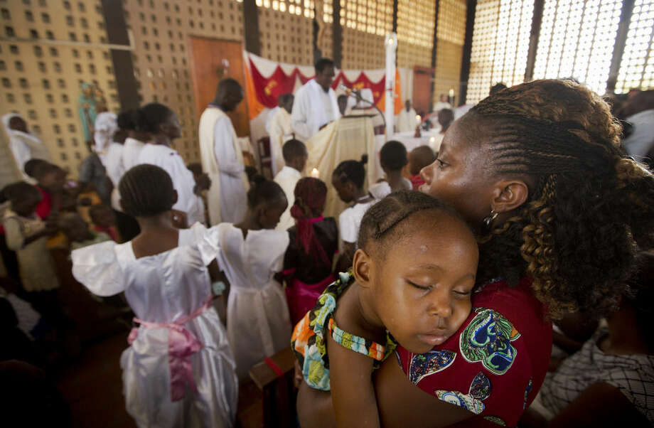 A child sleeps on her mother's shoulder during the service at the Our Lady of Consolation Church, which was attacked with grenades by militants almost three years ago, in Garissa, Kenya, Sunday, April 5, 2015. Easter Sunday's ceremony was laden with emotion for the several hundred members of Garissa's Christian minority, which is fearful following the recent attack on Garissa University College by al-Shabab, a Somalia-based Islamic extremist group, who singled out Christians for killing, though al-Shabab has a long record of killing Muslims over the years. (AP Photo/Ben Curtis)