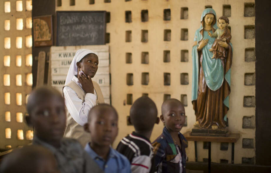 A nun wipes sweat from her neck during the service at the Our Lady of Consolation Church, which was attacked with grenades by militants almost three years ago, in Garissa, Kenya, Sunday, April 5, 2015. Easter Sunday's ceremony was laden with emotion for the several hundred members of Garissa's Christian minority, which is fearful following the recent attack on Garissa University College by al-Shabab, a Somalia-based Islamic extremist group, who singled out Christians for killing, though al-Shabab has a long record of killing Muslims over the years. (AP Photo/Ben Curtis)