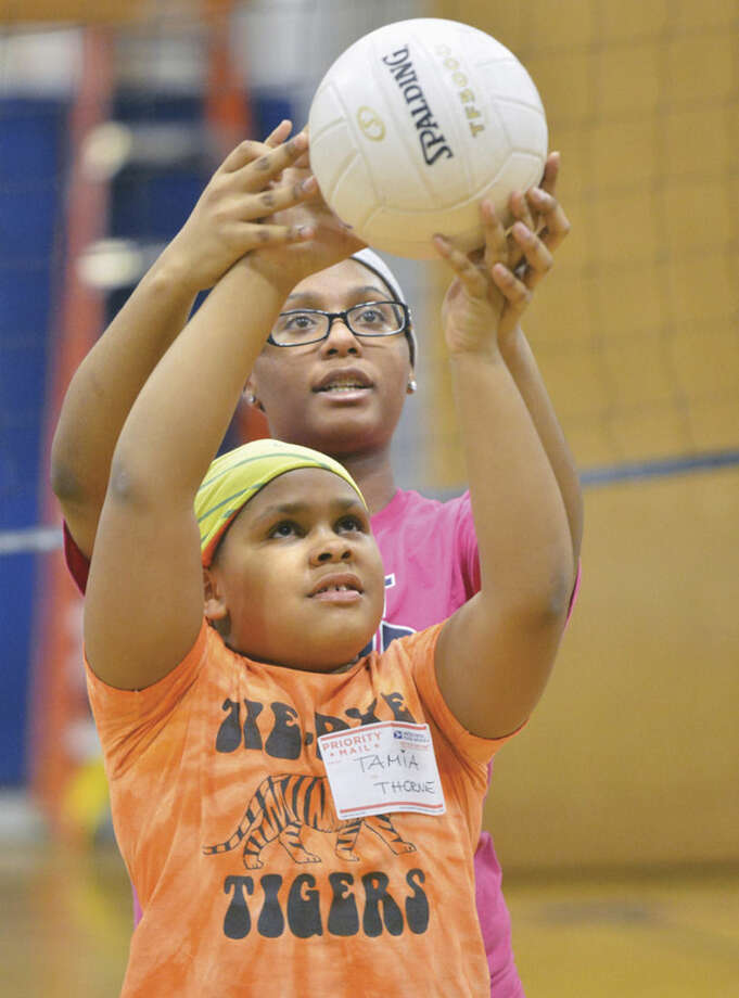 Hour photos/Alex von KleydorffAt left, Brien McMahon girls volleyball player Tonya-Lee Coley helps nine-year-old Tamia Thorne with some of the basics during the girls youth volleyball program at Kendall School. Above, Joy DeJaeger, center, addresses a group of young players.