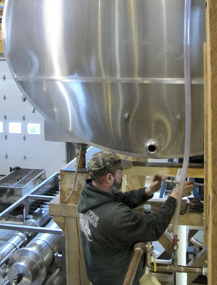 In this Wednesday, Feb. 3, 2016 photo, Wendell Downing works on a tank to hold sap to be boiled into maple syrup at Limlaw Family Maple Farm in West Topsham, Vt. A winter warmup has triggered sap to flow, launching an early start to the maple syrup season for some New England producers who tap trees early. Larger producers, like Limlaw, start tapping trees early so they can install tens of thousands of taps by the time the 4-6 week season is underway. (AP Photo/Lisa Rathke)