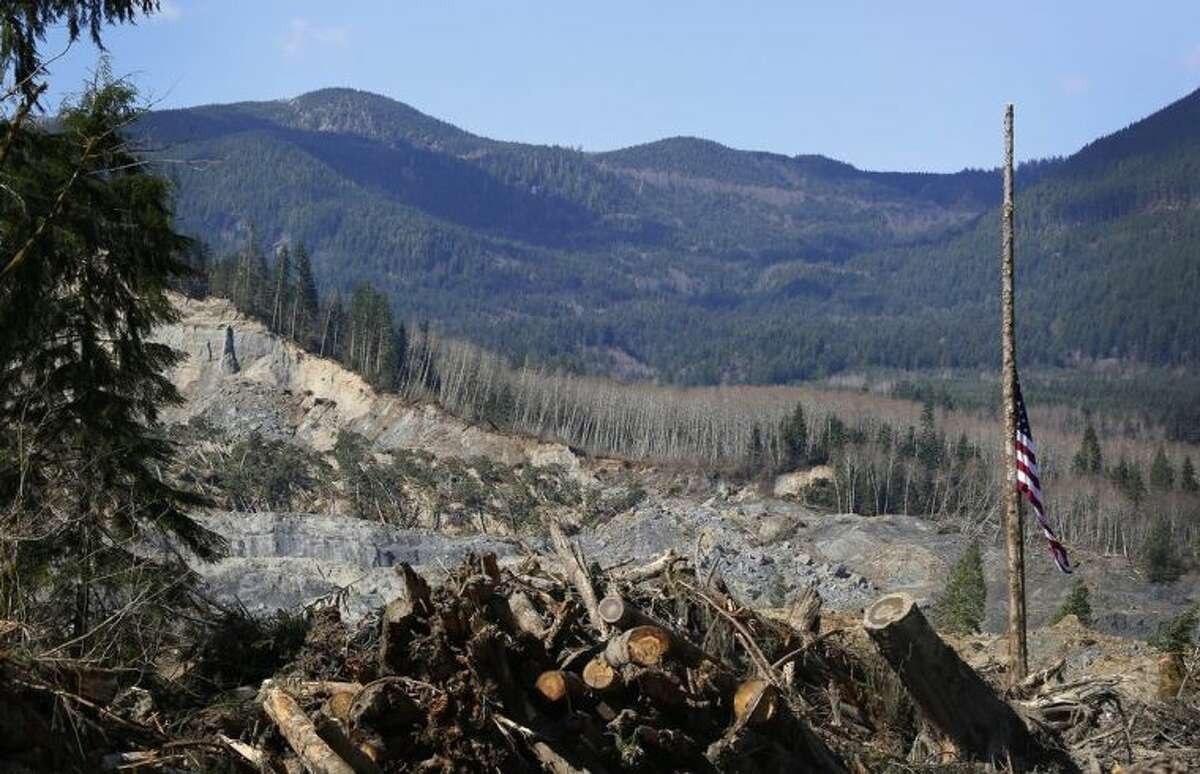 An American flag found in the debris hangs at half-staff on a single standing tree, with the slide site in the background, at the west site of the mudslide on Highway 530, near Oso, Wash., on Tuesday, April 1, 2014. The death toll from the March 22 mudslide has increased to 28. (AP Photo/The Seattle Times, Lindsey Wasson) SEATTLE OUT; USA TODAY OUT; MAGS OUT; TELEVISION OUT; NO SALES; MANDATORY CREDIT TO BOTH THE SEATTLE TIMES AND THE PHOTOGRAPHER