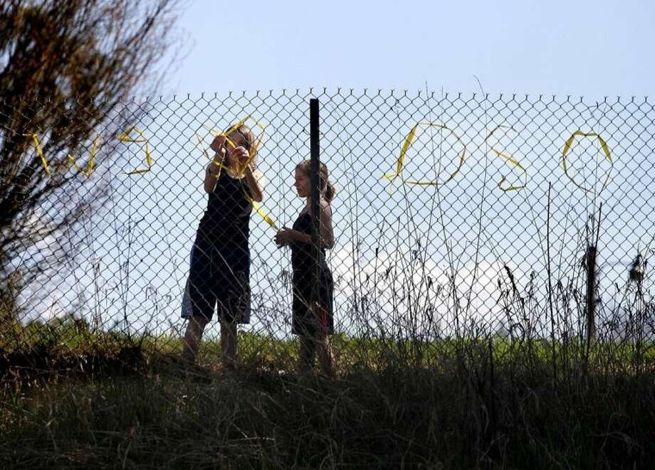 "Ava Yeckley and Darby Morgan, both Arlington, Wash. residents, put up a sign reading "" We heart Oso"" on the 530 highway Tuesday, April 1, 2014, near Arlington, Wash. (AP Photo/The Herald, Sofia Jaramillo)"