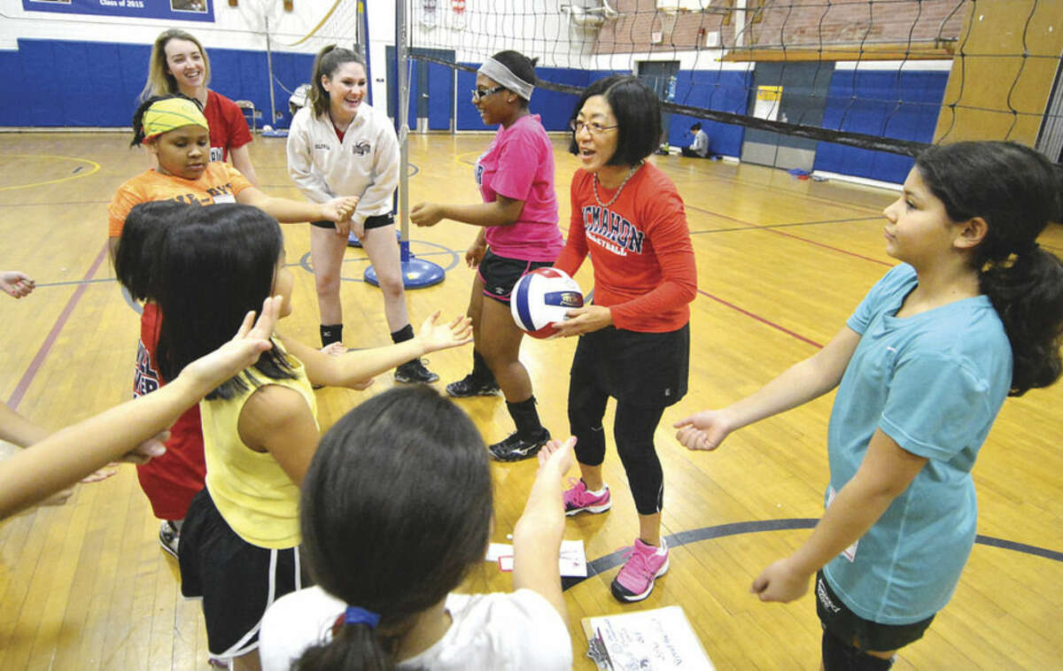 Hour Photo/Alex von Kleydorff Girls youth volleyball program coach Joy DeJaeger shows some of the different shots during a session at Kendall School