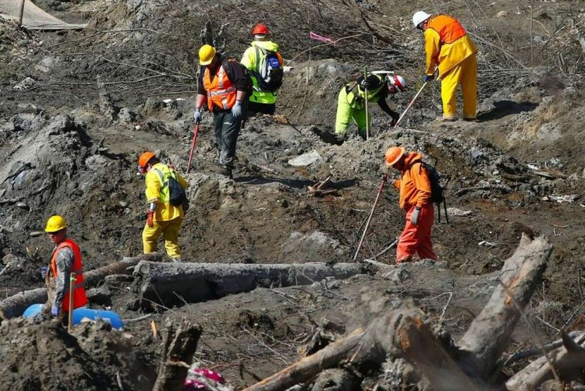Workers dig at a much drier mudslide site on the west side at the west site of the mudslide on Highway 530 near mile marker 37, near Oso, Wash., on Tuesday, April 1, 2014. The death toll from the March 22 mudslide has increased to 28. (AP Photo/The Seattle Times, Lindsey Wasson) SEATTLE OUT; USA TODAY OUT; MAGS OUT; TELEVISION OUT; NO SALES; MANDATORY CREDIT TO BOTH THE SEATTLE TIMES AND THE PHOTOGRAPHER