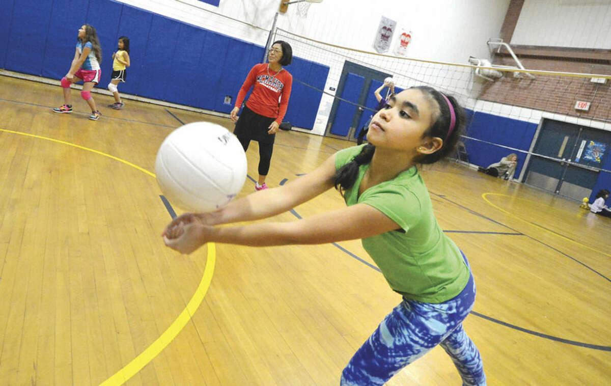 Hour Photo/Alex von Kleydorff Nine-year-old Mia Arbelaez of Norwalk works on some basic skills during the girls youth volleyball program at Kendall School in Norwalk last week.