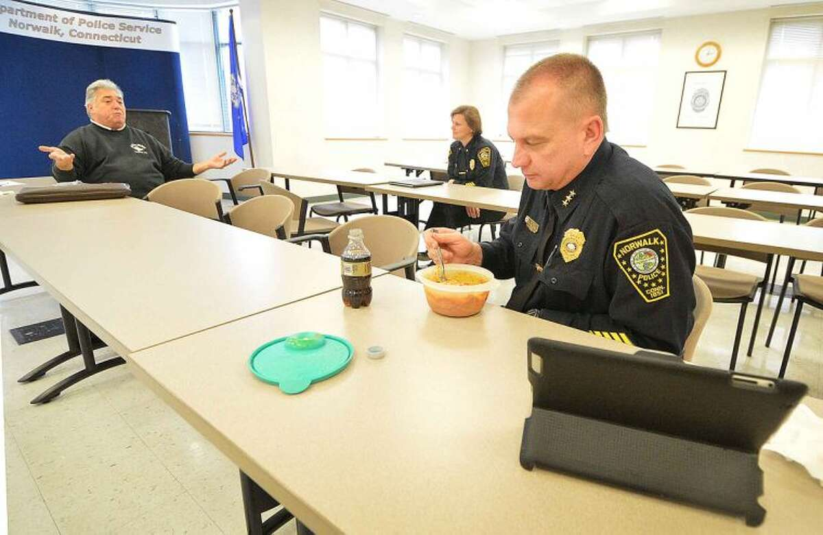 Hour Photo/Alex von Kleydorff Norwalk Police Chief Tom Kulhawik enjoys some leftover pasta he brought and Deputy Chief Sue Zecca talk about police matters during their Brown Bag Lunch with the public at Headquaters