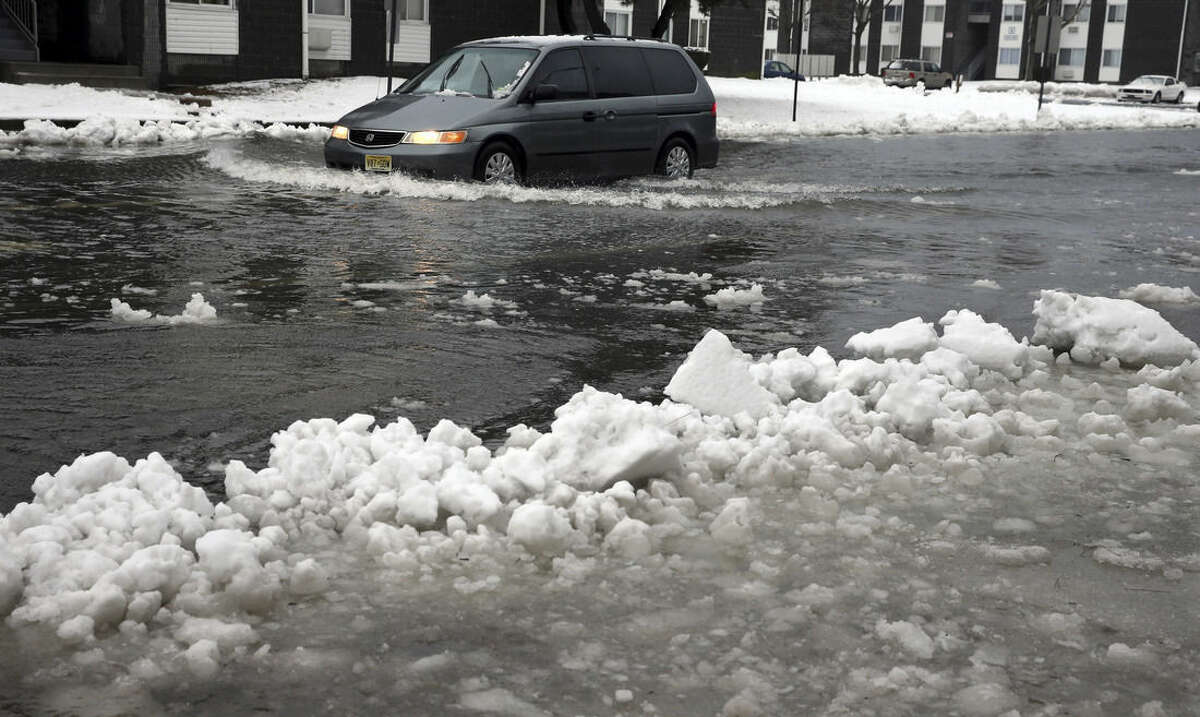 A van drives through a flooded street as ice and snow prevent drainage Saturday, Jan. 23, 2016, in Atlantic City, N.J. Most of the state was facing a blizzard warning from Friday evening until Sunday that called for up to 24 inches of snow, with the deepest accumulations in the central part of the state. (AP Photo/Mel Evans)