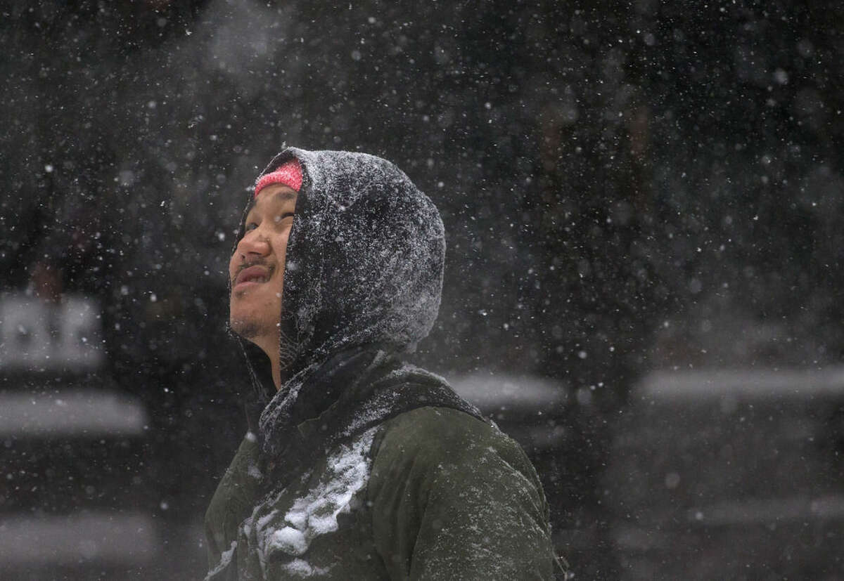 A man looks up into the falling snow as he walks along Broad Street in Lower Manhattan during a snowstorm, Saturday, Jan. 23, 2016, in New York. Millions of Americans awoke to heavy snow outside their doorsteps as a mammoth winter storm crawled up the East Coast. (AP Photo/Julie Jacobson)
