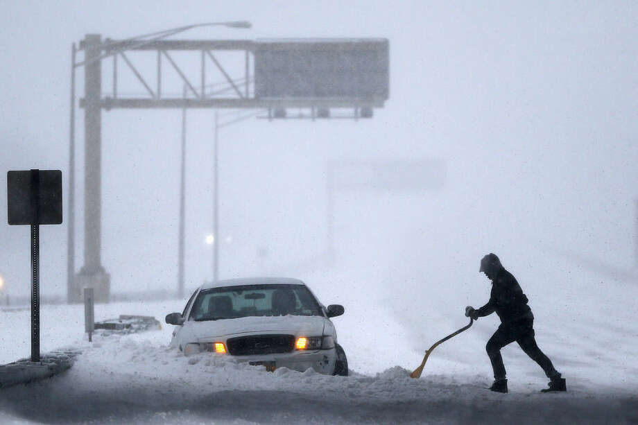 A motorist shovels snow to free up a vehicle on the New Jersey Turnpike during a snowstorm, Saturday, Jan. 23, 2016, in Port Reading, N.J. Towns across the state are hunkering down during a major snowstorm that hit overnight. (AP Photo/Julio Cortez)