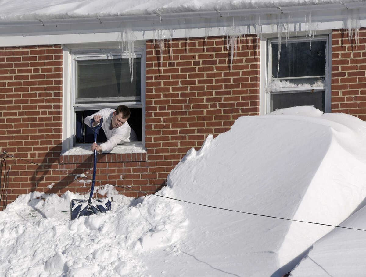 Shawn Covelly knocks snow off his awning, Sunday, Jan. 24, 2016, in Towson, Md. Millions of Americans were preparing to dig themselves out Sunday after a mammoth blizzard with hurricane-force winds and record-setting snowfall brought much of the East Coast to an icy standstill. (AP Photo/Steve Ruark)