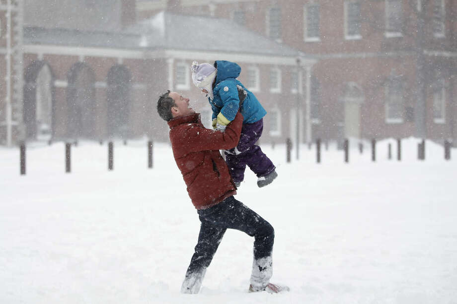 Dan Rafalin, left, lifts his daughter, Delila Rafalin, 5, while playing in heavy snowfall with their family on Independence Mall, Saturday, Jan. 23, 2016, in Philadelphia. (AP Photo/Matt Slocum)