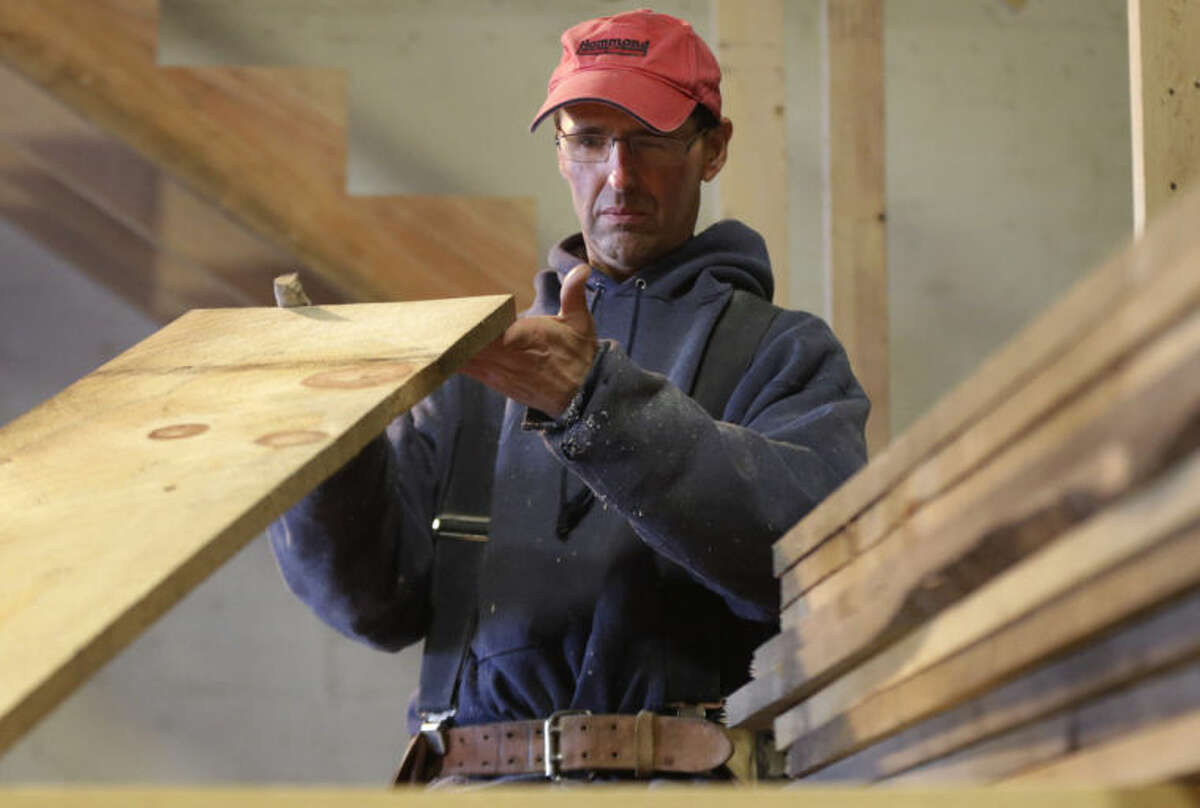 In this Wednesday, March 26, 2014 photo, Ken Voorhees examines a board for defects while building a stairway for a customer in Lisbon, Maine. Voorhees, who is self-employed, signed up for health insurance with Maine Health Community Options. The nonprofit cooperative is capturing about 80 percent of the customers in the state seeking coverage under the health care law. (AP Photo/Robert F. Bukaty)