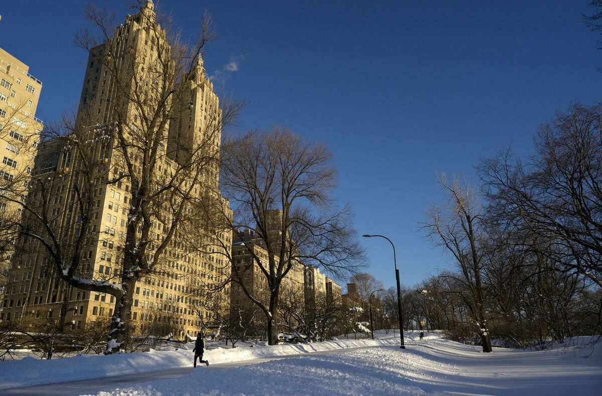 A pedestrian runs along a snow covered road in New York's Central Park, Sunday, Jan. 24, 2016, in the wake of a storm that dumped heavy snow along the East Coast. (AP Photo/Craig Ruttle)