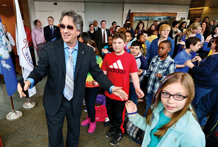 Hour photo / Erik Trautmann Board of Education member Jerry Pia leads the crowd in song as Stamford Education 4 Autism hosts a World Autism Awareness Day celebration at the Stamford Government Center Wednesday morning.