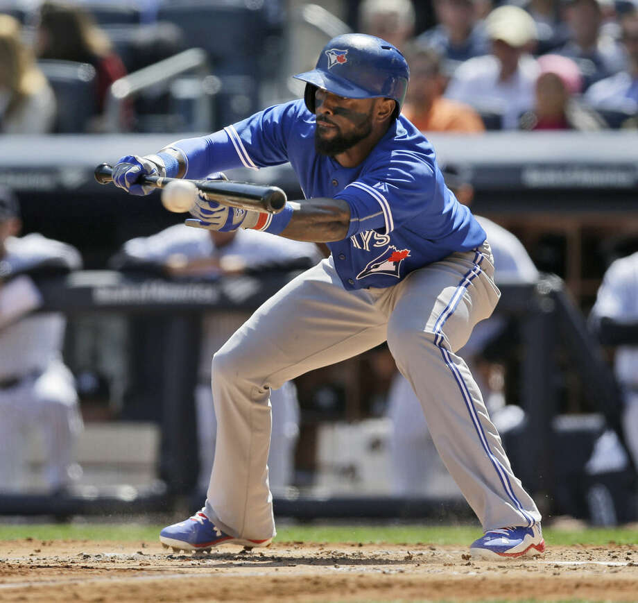 Toronto Blue Jays' Jose Reyes hits a bunt to score a run during the third inning of the baseball game against the New York Yankees at Yankee Stadium, Monday, April 6, 2015 in New York. (AP Photo/Seth Wenig)