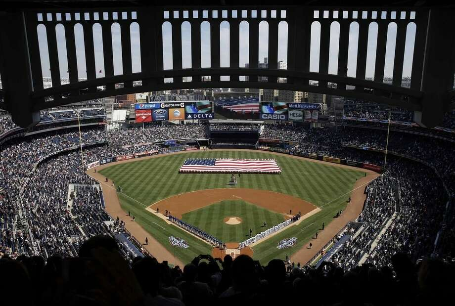 A large American flag is unfurled on the field before the opening day baseball game between the Toronto Blue Jays and the New York Yankees at Yankee Stadium, Monday, April 6, 2015 in New York. (AP Photo/Seth Wenig)