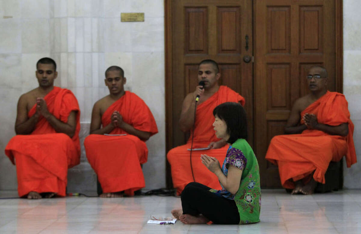 A Buddhist devotee offers prayers for passengers aboard the missing Malaysia Airlines Flight MH370 at a Buddhist temple in Kuala Lumpur, Malaysia, Tuesday, April 1, 2014. Investigators are conducting a forensic examination of the final recorded conversation between ground control and the cockpit of Malaysia Airlines Flight 370 before it went missing three weeks ago, the Malaysian government said Tuesday. (AP Photo/Lai Seng Sin)