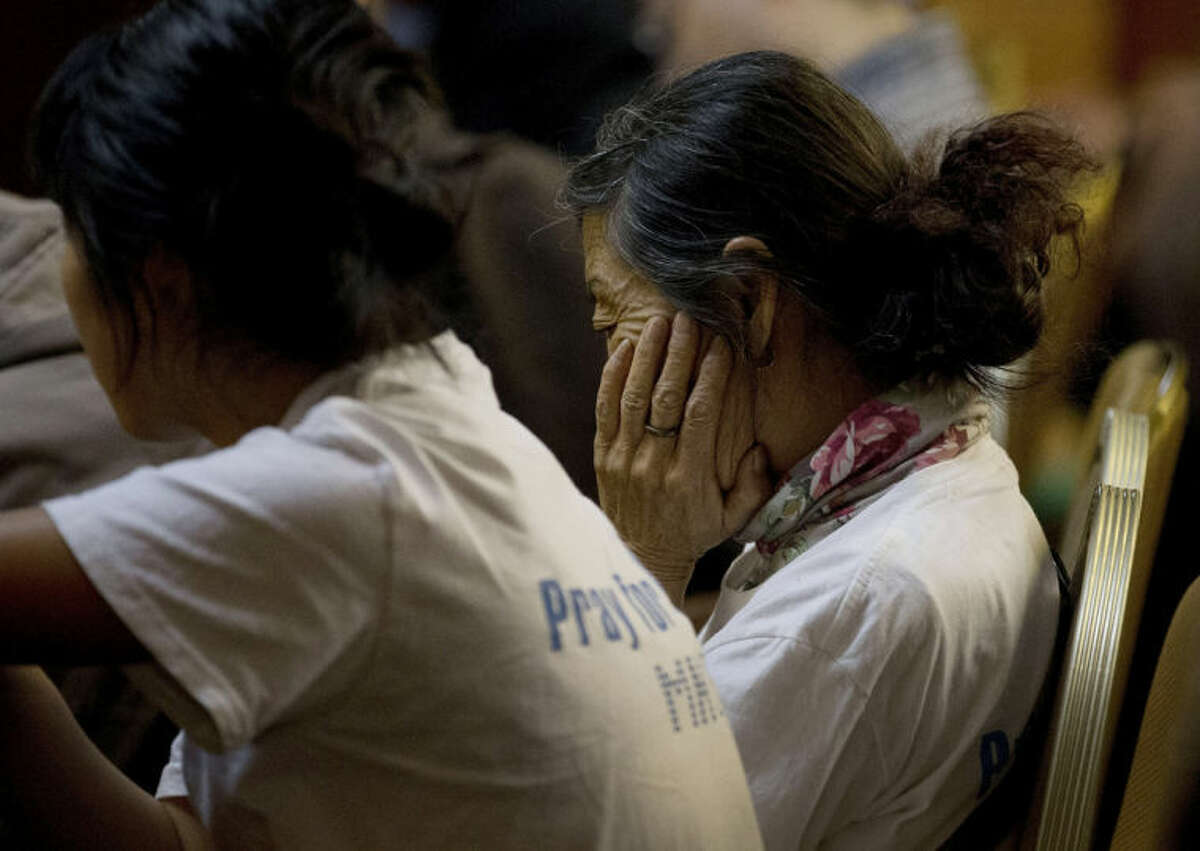 A woman, one of the relatives of Chinese passengers aboard the missing Malaysia Airlines flight MH370, reacts as she and others attend a daily briefing with Malaysian officials at a hotel in Beijing, China Tuesday, April 1, 2014. Although it has been slow, difficult and frustrating so far, the search for the missing Malaysia Airlines jet is nowhere near the point of being scaled back, Australia's Prime Minister Tony Abbott said. The three-week hunt for Flight 370 has turned up no sign of the Boeing 777, which vanished March 8 with 239 people bound for Beijing from Kuala Lumpur. (AP Photo/Andy Wong)
