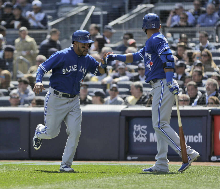 Toronto Blue Jays' Devon Travis, left, celebrates scoring a run with Jose Bautista during the third inning of the baseball game against the New York Yankees at Yankee Stadium, Monday, April 6, 2015 in New York. (AP Photo/Seth Wenig)