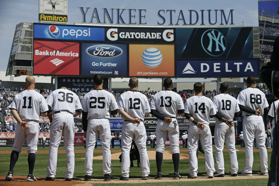 Members of the New York Yankees line hip on the baseline for player introductions and during the singing of the National Anthem in an opening day baseball game against the Toronto Blue Jays in New York, Monday, April 6, 2015. (AP Photo/Kathy Willens)