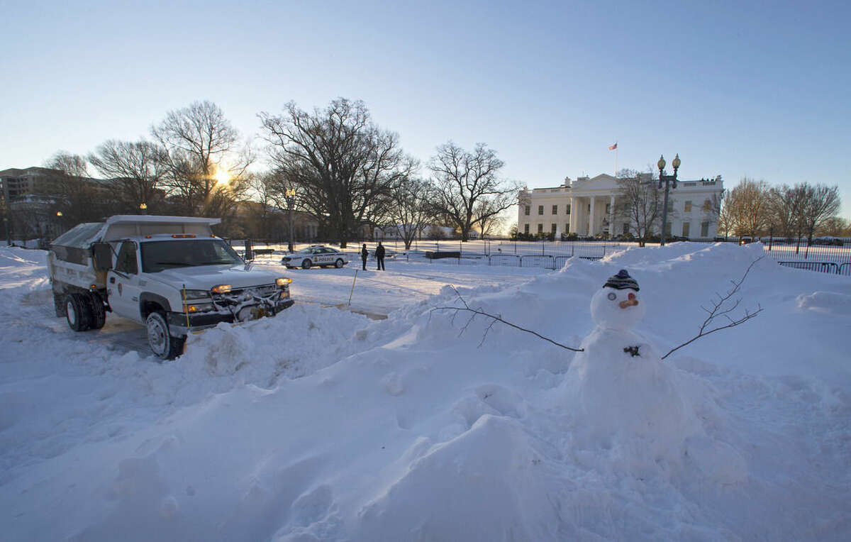 A National Park Service plows Pennsylvania Avenue in front of the White House in Washington on Sunday, Jan. 24, 2016. Millions of Americans were preparing to dig themselves out Sunday after a mammoth blizzard with hurricane-force winds and record-setting snowfall brought much of the East Coast to an icy standstill. (AP Photo/Jon Elswick)