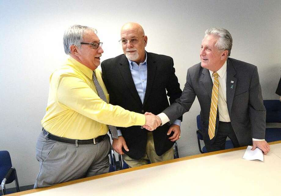 Hour Photo/Alex von Kleydorff City Clerk Rick McQuaid and Mayor Harry Rilling shake on it with My Three Sons owner and Councilman Jerry Petrini, all part of the new Norwalk Central Task Force.