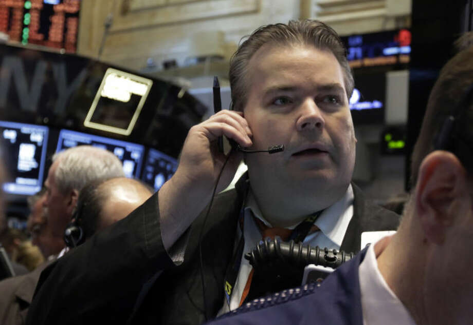 FILE - In this Wednesday, March 26, 2014, file photo, a trader works on the floor of the New York Stock Exchange. World stock markets pushed higher Wednesday April 2, 2014 on signs of a pickup in the U.S. economy and expectations of further stimulus in Japan. (AP Photo/Richard Drew, File)