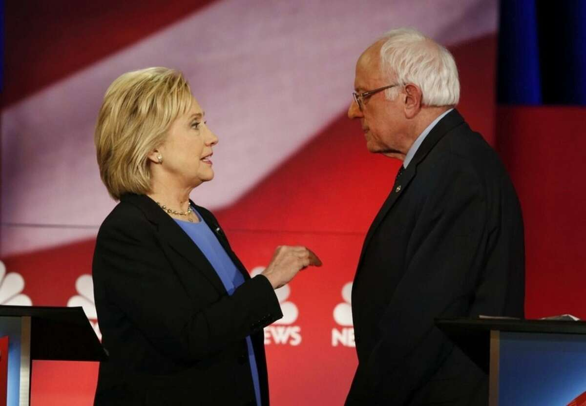 Democratic presidential candidate, Hillary Clinton and Democratic presidential candidate, Sen. Bernie Sanders, I-Vt. speak during a break at the NBC, YouTube Democratic presidential debate at the Gaillard Center, Sunday, Jan. 17, 2016, in Charleston, S.C. (AP Photo/Mic Smith)