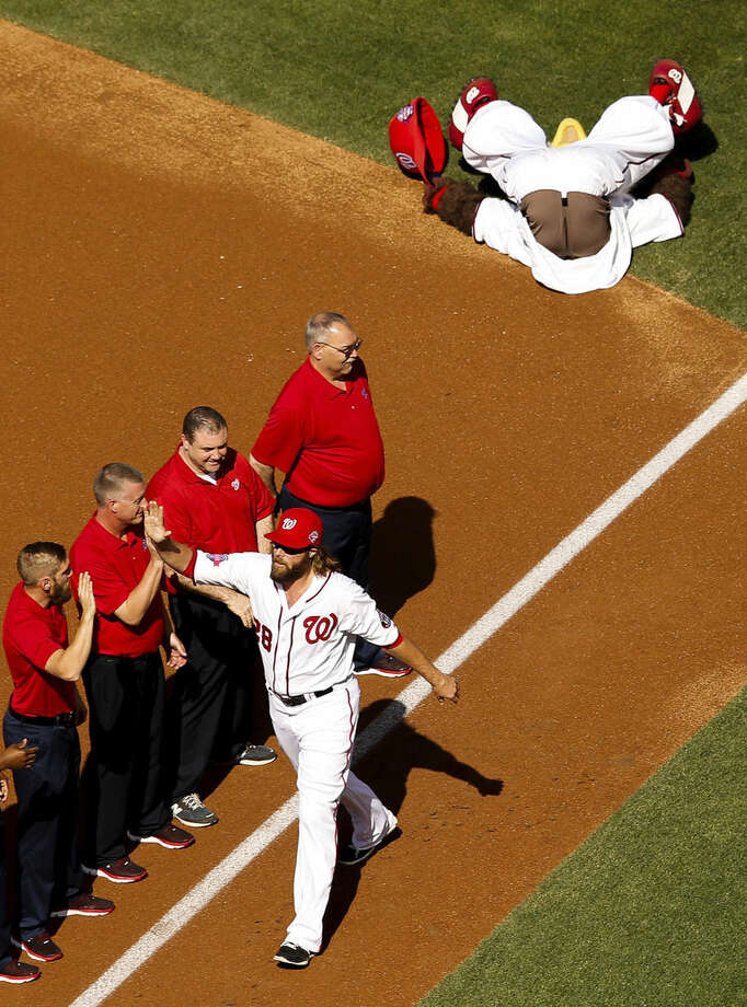 """Washington Nationals right fielder Jayson Werth high fives members of the ground crew after pushing over Washington Nationals mascot """"Screech"""" during an opening ceremony before a baseball game between the Washington Nationals and the New York Mets on opening day at at Nationals Park, Monday, April 6, 2015, in Washington. (AP Photo/Andrew Harnik)"""