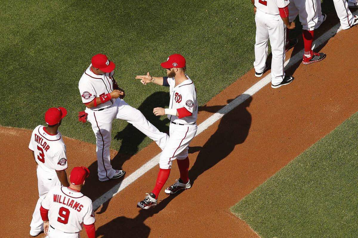 Washington Nationals shortstop Yunel Escobar and Washington Nationals left fielder Bryce Harper, center, greet each other during an opening ceremony before a baseball game between the Washington Nationals and the New York Mets on opening day at Nationals Park, Monday, April 6, 2015, in Washington. (AP Photo/Andrew Harnik)