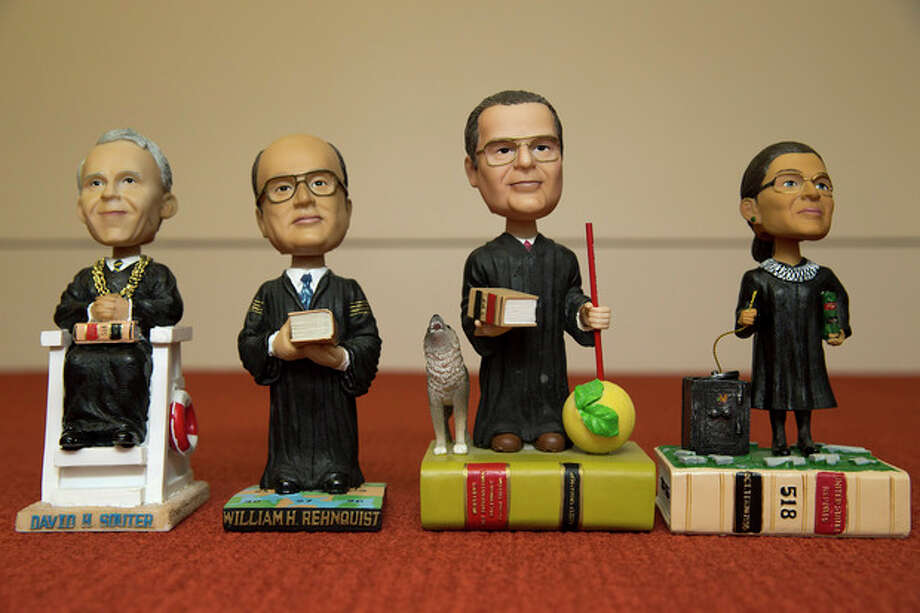 This photo taken Nov. 20, 2013 shows bobblehead dolls representing Supreme Court Justices, from left, David Souter, William Rehnquist, Antonin Scalia, and Ruth Ginsburg, in Washington. They are some of the rarest bobblehead dolls ever produced. They're released erratically. They're given away for free, not sold. And if you get a certificate to claim one, you have to redeem it at a Washington, DC, law office. The limited edition bobbleheads of U.S. Supreme Court justices are the work of law professor Ross Davies, who has been creating them for the past ten years. When finished, they arrive unannounced on the real justices' desks, secreted there by unnamed confederates. And fans will go to some lengths to get one. (AP Photo/Jacquelyn Martin) / AP