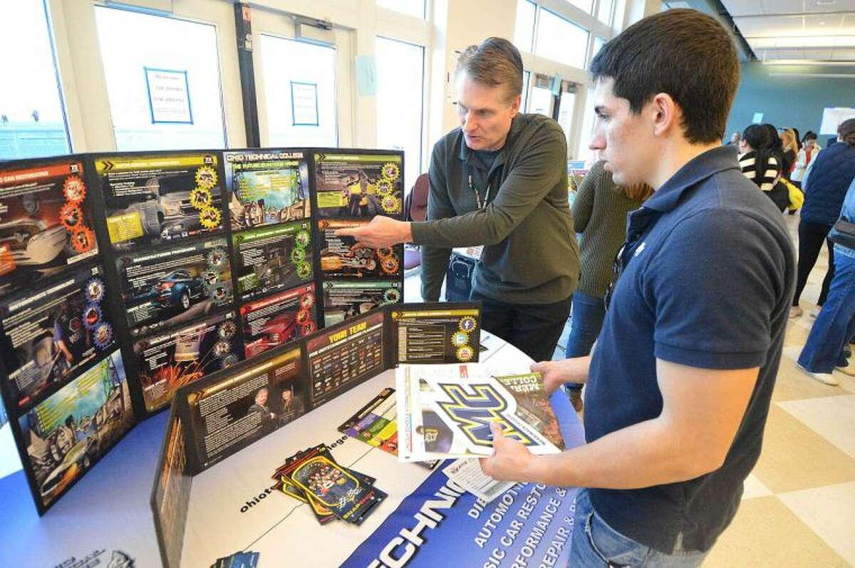 Hour Photo/Alex von Kleydorff. Massimo Diferico speaks with admissions representative Ron Zelman about Ohio Technical College at the Citywide College Fair at Brien McMahon High School