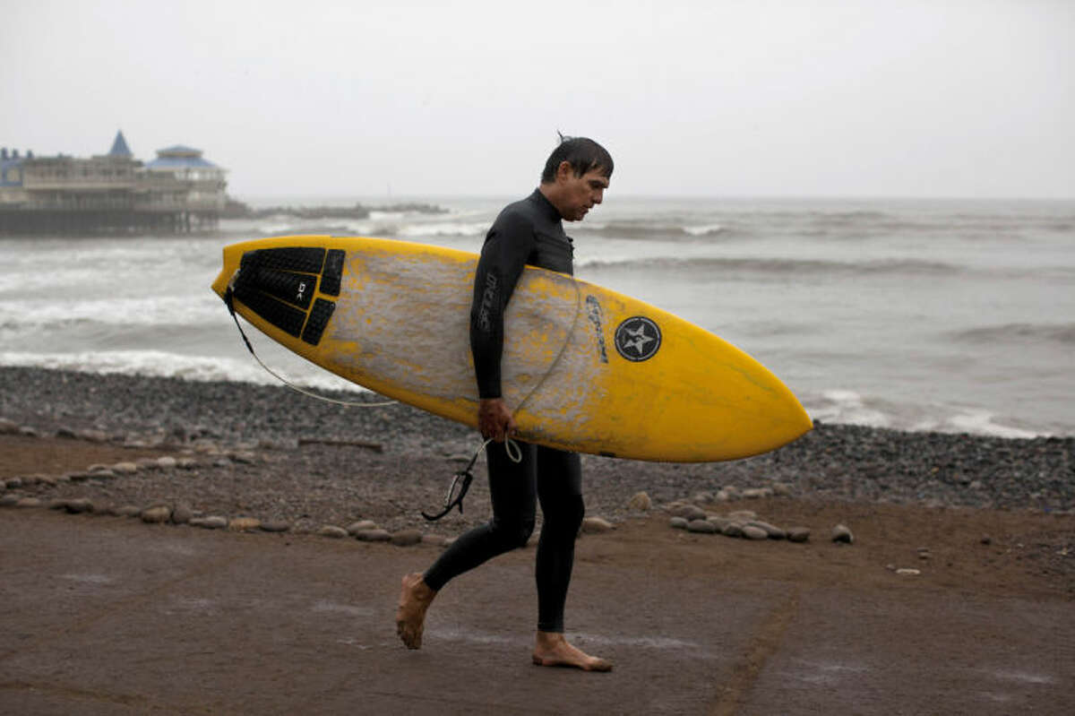 A man walks with his surfboard after a morning of surfing in the Pacific Ocean waters of Makaha beach, in Lima, Peru, Wednesday, April 2, 2014. Chilean authorities discovered surprisingly light damage Wednesday from a magnitude-8.2 quake that struck in the Pacific Ocean, Tuesday evening, near the mining port of Iquique, about 87 miles from the Peruvian border. Tsunami warnings issued for Chile, Peru and Ecuador have been lifted. Six deaths have been reported. (AP Photo/Rodrigo Abd)