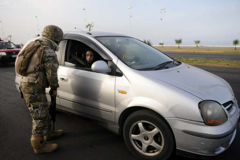 A Chilean soldier inspects a car in the northern town of Iquique, Chile, after magnitude 8.2 earthqauke struck the northen coast of Chile, Wednesday, April 2, 2014. Chilean President Michelle Bachelet flew to the region to review damage in daylight after declaring a state of emergency and sending a military plane with 100 anti-riot police to join 300 soldiers who were deployed to prevent looting and round up escaped prisoners. (AP Photo/Cristian Viveros) NO PUBLICAR EN CHILE