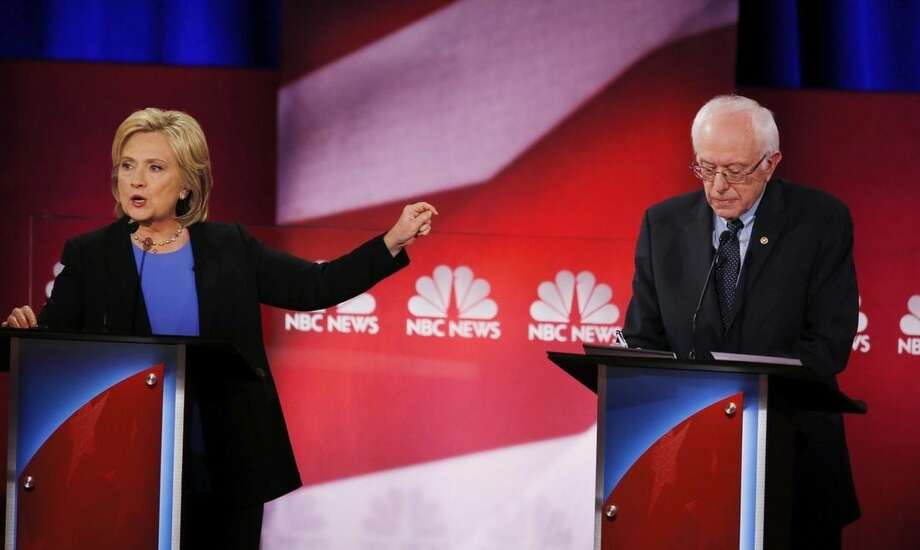 Democratic presidential candidate, Hillary Clinton gestures towards Democratic presidential candidate, Sen. Bernie Sanders, I-Vt, during the NBC, YouTube Democratic presidential debate at the Gaillard Center, Sunday, Jan. 17, 2016, in Charleston, S.C. (AP Photo/Mic Smith)