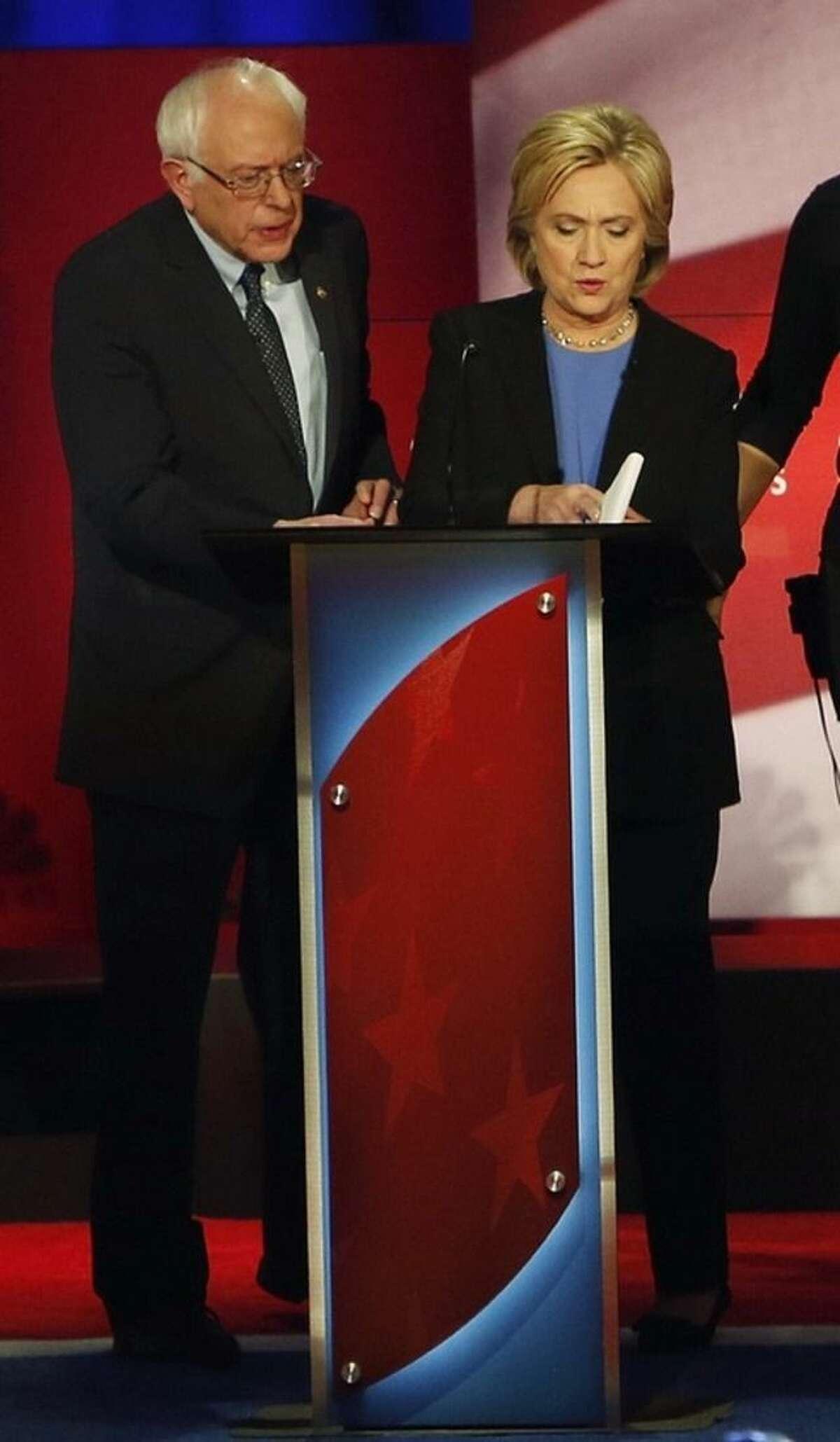 Democratic presidential candidates, Hillary Clinton and Sen. Bernie Sanders, I-Vt. confer during a break at the NBC, YouTube Democratic presidential debate at the Gaillard Center, Sunday, Jan. 17, 2016, in Charleston, S.C. (AP Photo/Mic Smith)
