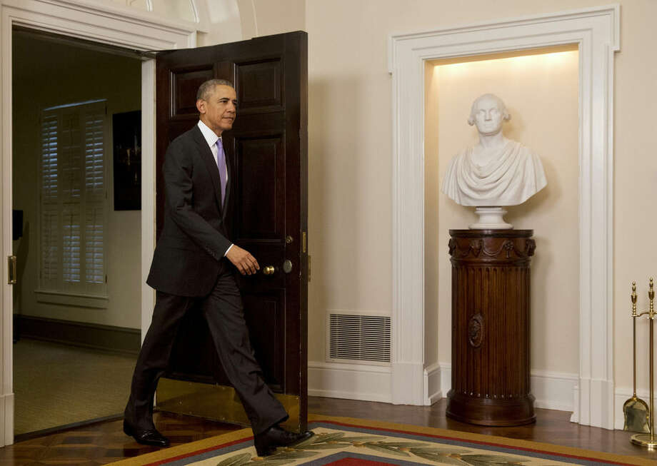 President Barack Obama enters the Cabinet Room of the White House to speak about the release of Americans by Iran, Sunday, Jan. 17, 2016, in Washington. (AP Photo/Jacquelyn Martin)