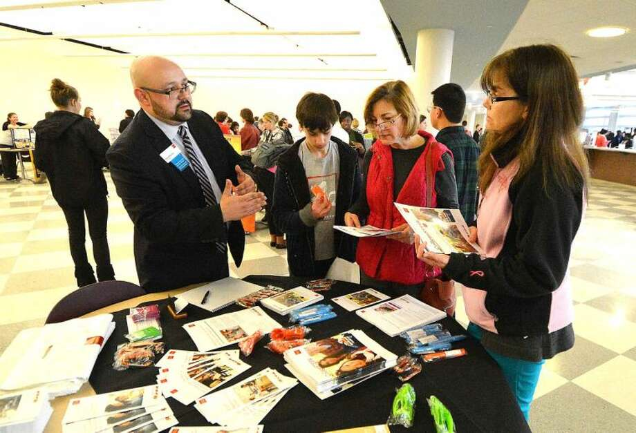 Hour Photo/Alex von Kleydorff David Molina, Westport Ave Wells Fargo Branch Manager goes over some of the finance options during the Citywide College Fair at Brien McMahon