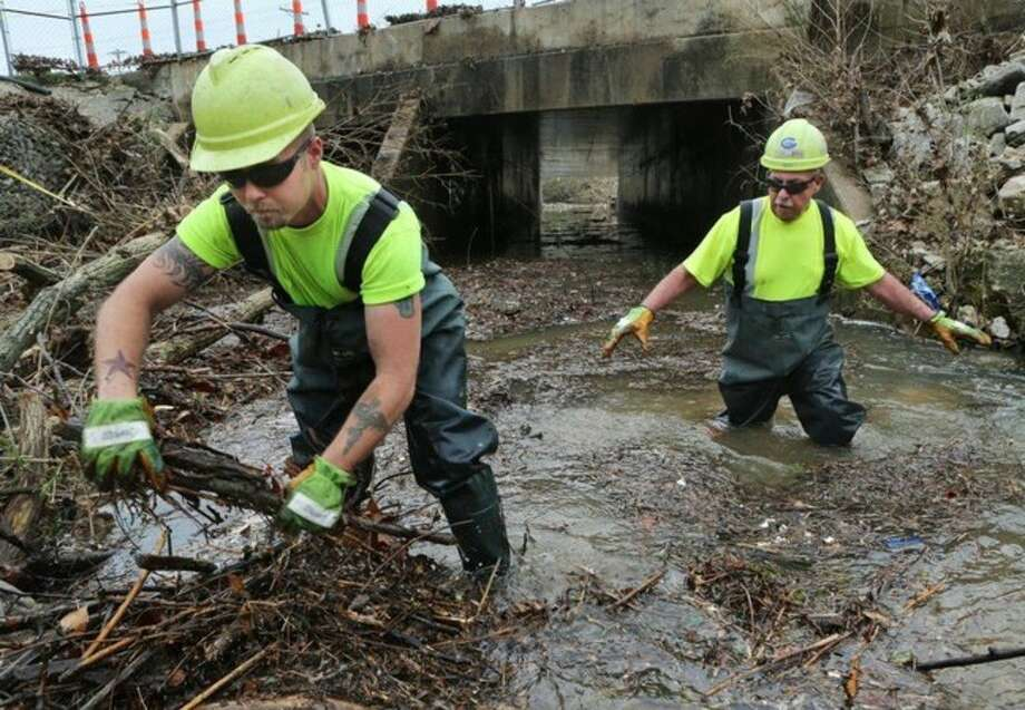 MoDot workers Clay LaPlante, left, and Jim Jamison clear debris from Fish Pot Creek in Ballwin, Mo., Wednesday, April 8, 2015, that was blocking the Manchester Road bridge near New Ballwin Road. The blockage came after the storm on Tuesday causing the area around the bridge to flood, including the Ballwin Auto Center and the Ballwin Laundromat. (AP Photo/St. Louis Post-Dispatch, J.B. Forbes) EDWARDSVILLE INTELLIGENCER OUT, THE ALTON TELEGRAPH OUT