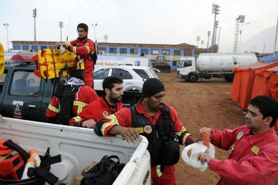 Rescue personnel get ready to go into action in the northern town of Iquique, Chile, after magnitude 8.2 earthqauke struck the northen coast of Chile, Wednesday, April 2, 2014. Authorities lifted tsunami warnings for Chile's long coastline early Wednesday. Six people were crushed to death or suffered fatal heart attacks, a remarkably low toll for such a powerful shift in the Earth's crust. (AP Photo/Cristian Viveros) NO PUBLICAR EN CHILE